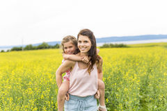 在黄色花的愉快的家庭母亲和儿童女儿容忍在自然在夏天 库存图片