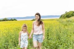 在黄色花的愉快的家庭母亲和儿童女儿容忍在自然在夏天 库存照片