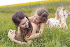 在黄色花的愉快的家庭母亲和儿童女儿容忍在自然在夏天 免版税图库摄影