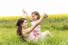 在黄色花的愉快的家庭母亲和儿童女儿容忍在自然在夏天 免版税库存图片