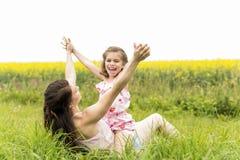 在黄色花的愉快的家庭母亲和儿童女儿容忍在自然在夏天 免版税库存照片
