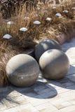在黄色草背景的大灰色具体球形和装饰、现代公园和庭院设计 免版税库存图片
