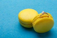 在黄色蛋白杏仁饼干的一只钻戒在蓝色背景 结婚的提议 安置文本 库存照片