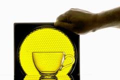 在黄色蜂窝背景的透明mugholds手  免版税库存图片