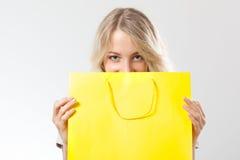 在黄色购物袋之后的白肤金发的妇女 免版税库存照片
