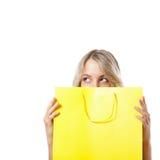 在黄色购物袋之后的白肤金发的妇女 免版税库存图片