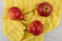 在黄色餐巾的三个红色梨在木桌上 库存图片