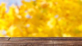 在黄色bokeh抽象背景的土气木桌 库存照片