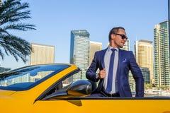 在黄色cabrio汽车的成功的杨商人 免版税图库摄影