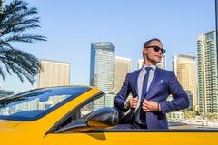 在黄色cabrio汽车的成功的杨商人 免版税库存照片