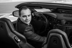 在黄色cabrio汽车的成功的杨商人 图库摄影