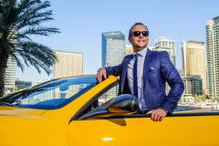 在黄色cabrio汽车的成功的杨商人 库存图片