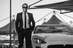 在黄色cabrio汽车的成功的杨商人 免版税库存图片