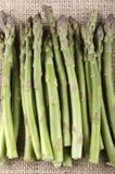 在黄麻布料的绿色芦笋 免版税图库摄影
