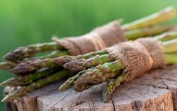 在黄麻的被包裹的芦笋在木背景 免版税库存照片