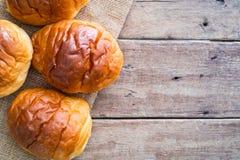 在黄麻袋布料的新鲜的黄油卷面包小圆面包在与拷贝空间的木桌上 免版税库存图片
