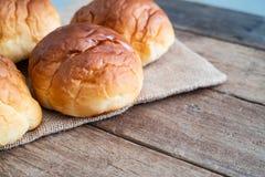 在黄麻袋布料的新鲜的黄油卷面包小圆面包在木桌上 免版税库存照片