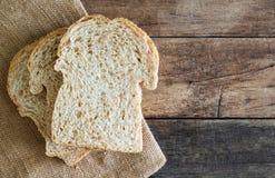 在黄麻袋布料的被堆积的切片全麦三明治面包在木桌上 免版税库存照片