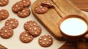 在黏土杯子的热的牛奶在有新鲜的被烘烤的巧克力饼干的老木切板 股票录像