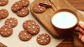 在黏土杯子的热的牛奶在有新鲜的被烘烤的巧克力饼干的老木切板 股票视频