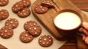 在黏土杯子的热的牛奶在老木切板用在羊皮纸的新鲜的被烘烤的巧克力曲奇饼 股票录像