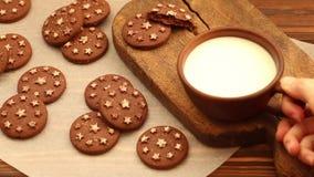 在黏土杯子的热的牛奶在老木切板用在羊皮纸的新鲜的被烘烤的巧克力曲奇饼 影视素材