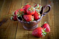 在黏土杯的草莓在一张木桌上 库存图片