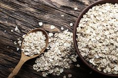 在黏土板材的未加工的燕麦粥剥落在木背景 健康碳水化合物早餐 库存图片