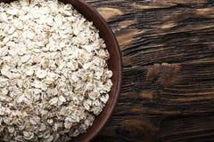 在黏土板材的未加工的燕麦粥剥落在木背景 健康碳水化合物早餐 库存照片