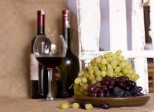 在黏土的蓝色和绿色葡萄变褐盘 有红色的瓶和 免版税图库摄影