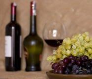 在黏土的蓝色和绿色葡萄变褐盘 有红色的瓶和 图库摄影