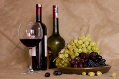 在黏土的蓝色和绿色葡萄变褐盘 有红色的瓶和 免版税库存照片