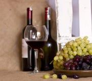 在黏土的蓝色和绿色葡萄变褐盘 有红色的瓶和 库存照片
