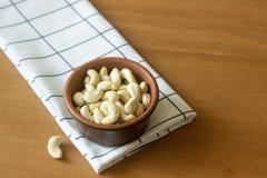 在黏土碗的腰果在一张木桌上 库存图片