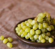 在黏土褐色盘的绿色葡萄 图库摄影
