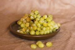 在黏土褐色盘的绿色葡萄 免版税图库摄影