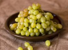 在黏土褐色盘的绿色葡萄 免版税库存照片