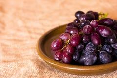 在黏土褐色盘的蓝色葡萄 库存图片