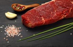 在黑人委员会的肉被切的未加工的牛排和香料 库存图片