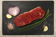 在黑人委员会的肉被切的未加工的牛排和香料 免版税库存图片