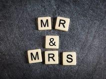 在黑人板岩背景拼写先生&夫人的瓦片上写字 免版税库存照片