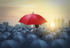 在黑伞中的独特的红色伞 免版税库存照片