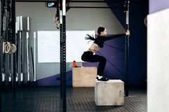 在黑体育衣裳打扮的亭亭玉立的深色头发的女孩做着在箱子的蹲坐在健身房 库存图片