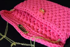 在黑光滑的背景是一桃红色妇女` s在她的肩膀的被编织的袋子与金轻便小床和开罐头用具和反射 图库摄影