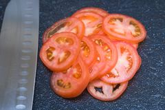 在黑切板的稀薄地切的好的蕃茄 免版税库存照片