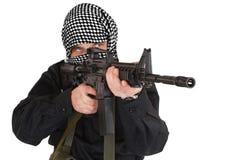 在黑制服和黑白shemagh打扮的叛乱者与m4攻击步枪 免版税图库摄影