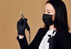 在黑医学面具和手套的大师准备经营与特别钉子和刷子的修指甲设备电雕刻师 库存照片