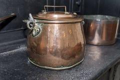 在黑古色古香的煤气炉的维多利亚女王时代的铜砂锅平底锅在a 免版税库存照片