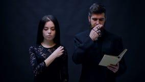 在黑和教士打扮的女孩施洗在黑背景 教士在黑背景祈祷 宗教尼姑 股票录像
