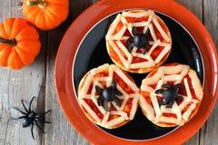 在黑和橙色板材的万圣夜蜘蛛网微型薄饼 库存图片